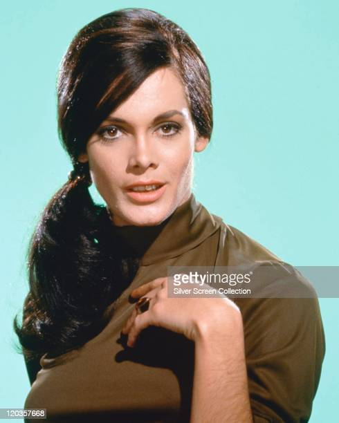 Martine Beswick British actress and model wearing a dark green polo neck sweater in a studio portrait against a light blue background circa 1965