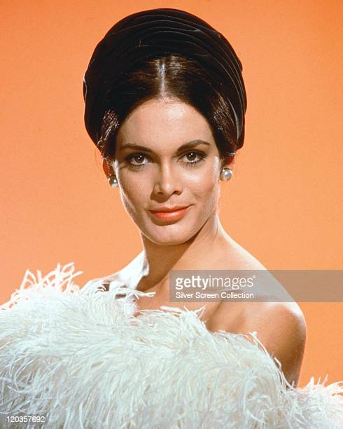 Martine Beswick British actress and model wearing a strapless outfit made of white ostrich feathers in a studio portrait against a light orange...