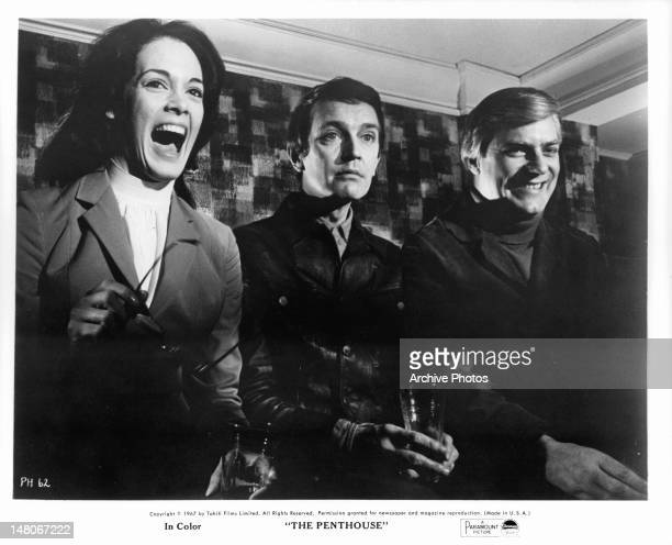 Martine Beswick Tony Beckley and Norman Rodway gathered together in a scene from the film 'The Penthouse' 1967