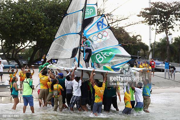 Martine Grael of Brazil and Kahena Kunze of Brazil are carried ashore as they celebrate winning gold in the Women's 49er FX class at the Marina da...