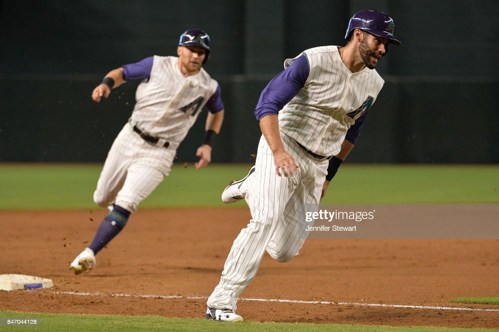 J.D. Martinez #28 and Brandon Drury #27 of the Arizona Diamondbacks both round third base to score in the first inning of the MLB game against the Colorado Rockies at Chase Field on September 14, 2017 in Phoenix, Arizona.