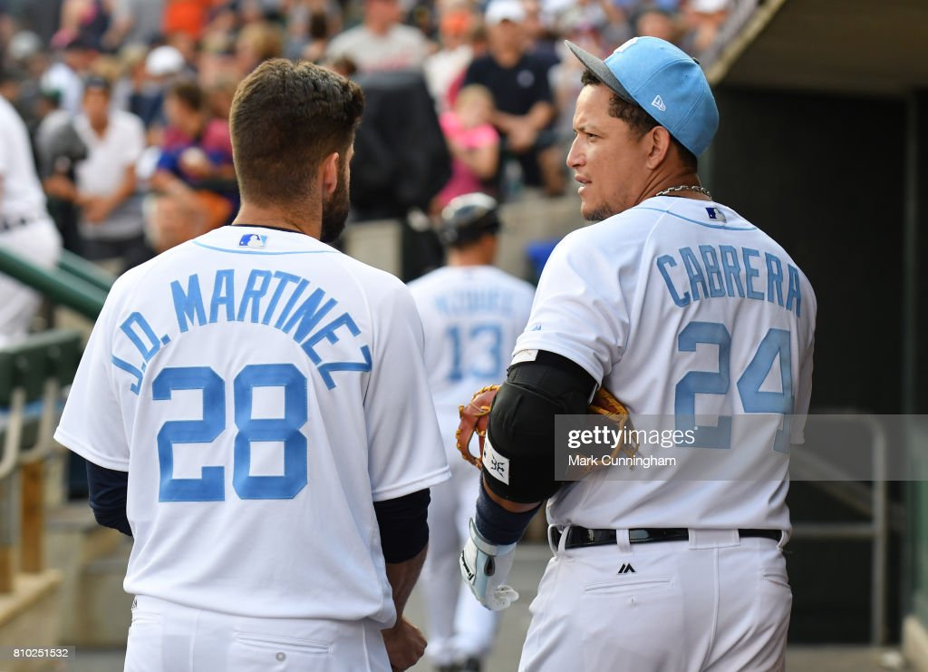 J.D. Martinez #28 and Miguel Cabrera #24 of the Detroit Tigers talk together in the dugout after the game against the Tampa Bay Rays while wearing a special blue jersey and hat for prostate cancer awareness on Father's Day Weekend at Comerica Park on June 17, 2017 in Detroit, Michigan. The Rays defeated the Tigers 3-2.