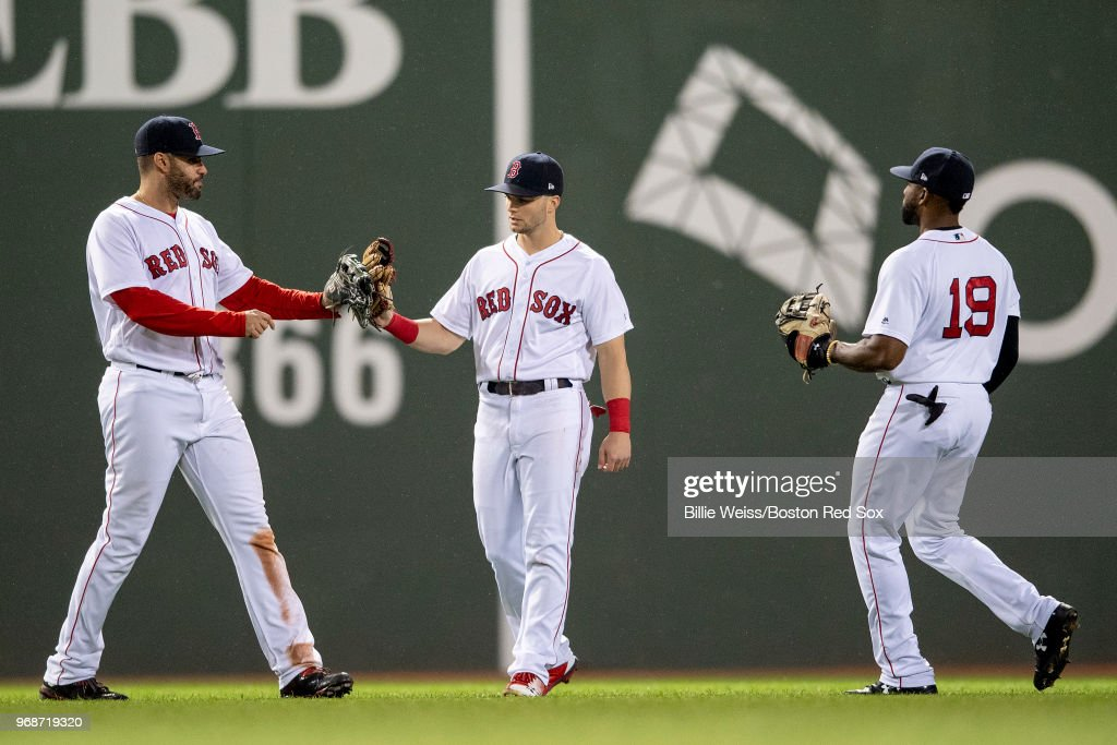 J.D. Martinez #28, Andrew Benintendi #16, and Jackie Bradley Jr. #19 of the Boston Red Sox celebrate a victory against the Detroit Tigers on June 6, 2018 at Fenway Park in Boston, Massachusetts.