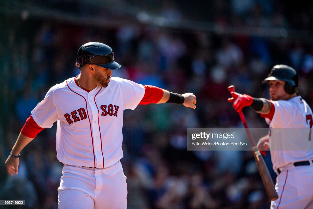 J.D. Martinez #28 high fives Christian Vazquez #7 of the Boston Red Sox after scoring during the eighth inning of a game against the Toronto Blue Jays on May 30, 2018 at Fenway Park in Boston, Massachusetts.