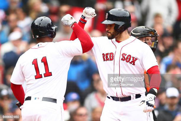 D Martinez high fives Rafael Devers of the Boston Red Sox as he crosses home plate after hitting a solo home run in the third inning of a game...