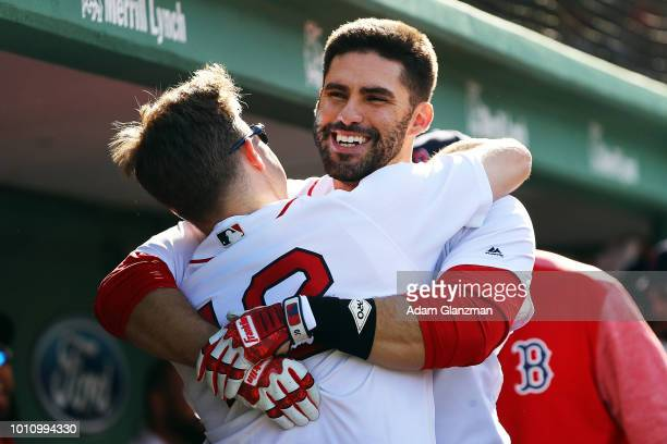 D Martinez hugs Brock Holt of the Boston Red Sox when he returns to the dugout after hitting a solo home run in the fourth inning of a game against...