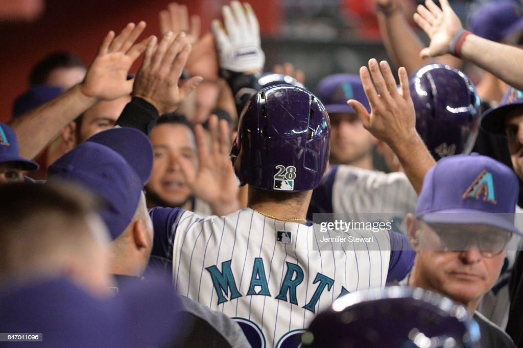J.D. Martinez #28 of the Arizona Diamondbacks is congratulated in the dugout after scoring in the first inning against the Colorado Rockies at Chase Field on September 14, 2017 in Phoenix, Arizona.