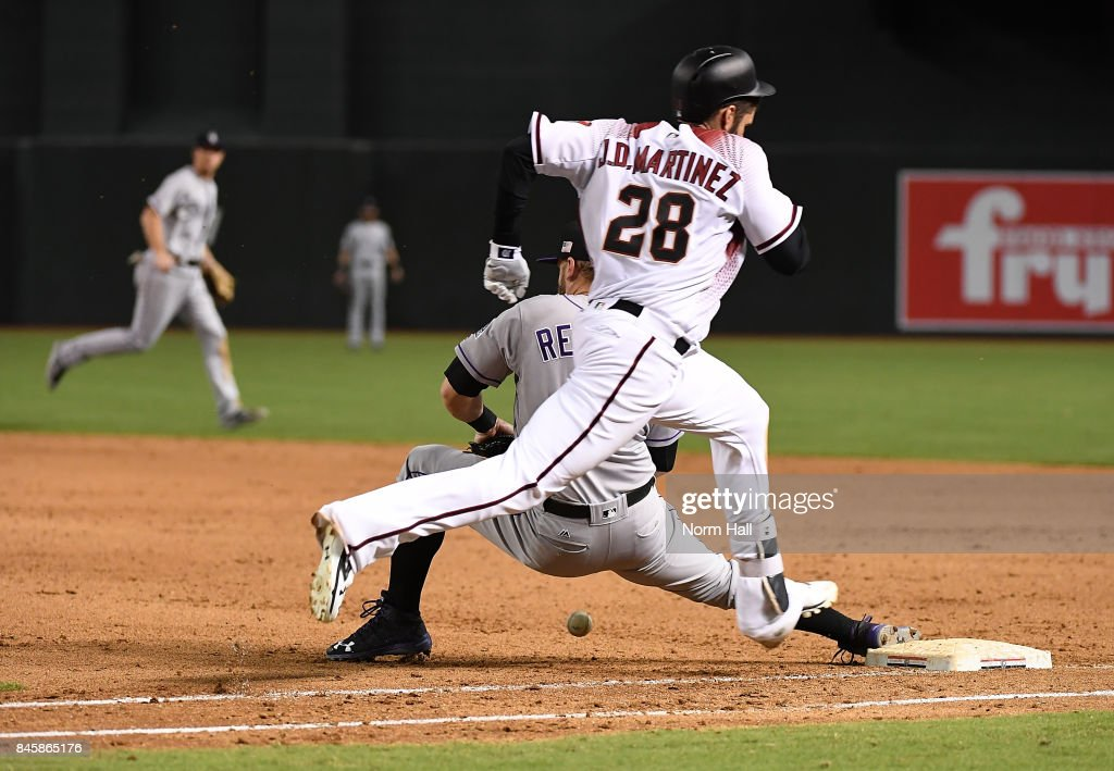 JD Martinez #28 of the Arizona Diamondbacks safely reaches first base on a ball hit to third base as Mark Reynolds #12 of the Colorado Rockies cannot come up with a throw in the dirt during the eighth inning at Chase Field on September 11, 2017 in Phoenix, Arizona. Rockies won 5-4.