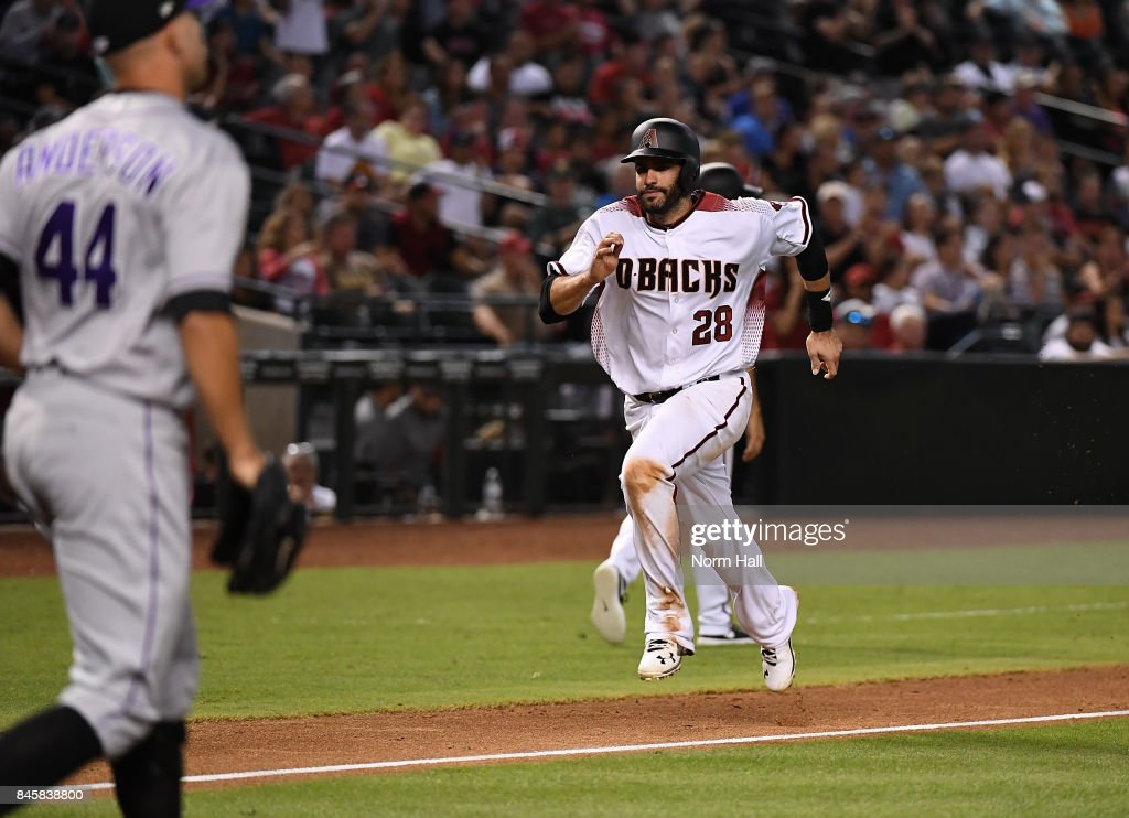 JD Martinez #28 of the Arizona Diamondbacks scores on a sacrific fly by teammate Adam Rosales #9 against the Colorado Rockies during the fourth inning at Chase Field on September 11, 2017 in Phoenix, Arizona.