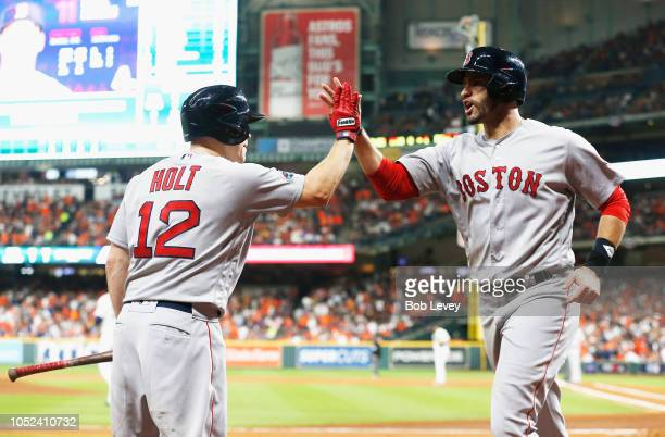 D Martinez of the Boston Red Sox celebrates with Brock Holt after scoring a run in the first inning against the Houston Astros during Game Four of...
