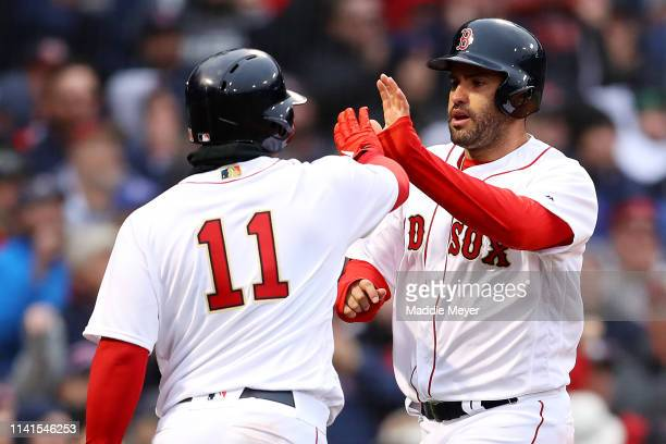 D Martinez of the Boston Red Sox celebrates with Rafael Devers after scoring a run against the Toronto Blue Jays during the eighth inning of the Red...