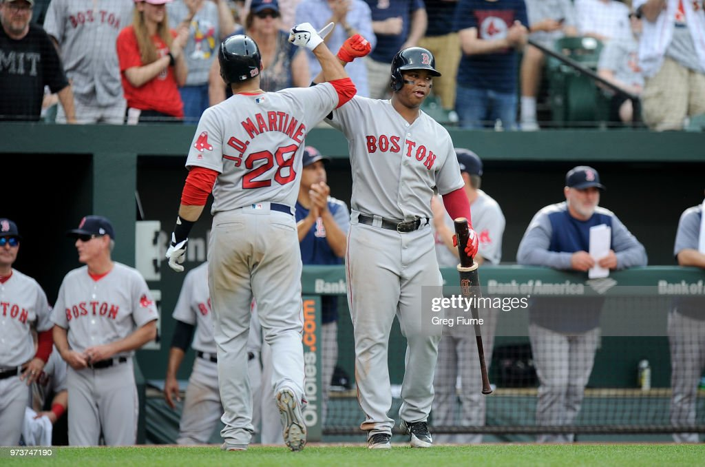 J.D. Martinez #28 of the Boston Red Sox celebrates with Rafael Devers #11 after hitting a home run in the seventh inning against the Baltimore Orioles at Oriole Park at Camden Yards on June 13, 2018 in Baltimore, Maryland.