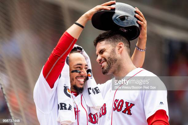 D Martinez of the Boston Red Sox has his helmet removed by Mookie Betts after hitting a solo home run during the fourth inning of a game against the...