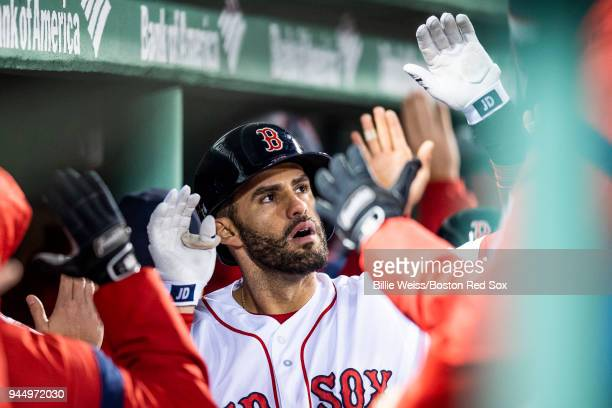 D Martinez of the Boston Red Sox high fives teammates after hitting a grand slam home run during the fifth inning of a game against the New York...