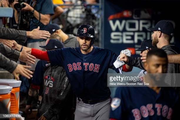 D Martinez of the Boston Red Sox high fives teammates during the tenth inning of game three of the 2018 World Series against the Los Angeles Dodgers...