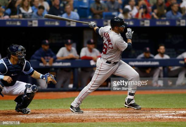 D Martinez of the Boston Red Sox hits an RBI single in front of catcher Wilson Ramos of the Tampa Bay Rays to score Mookie Betts during the fifth...
