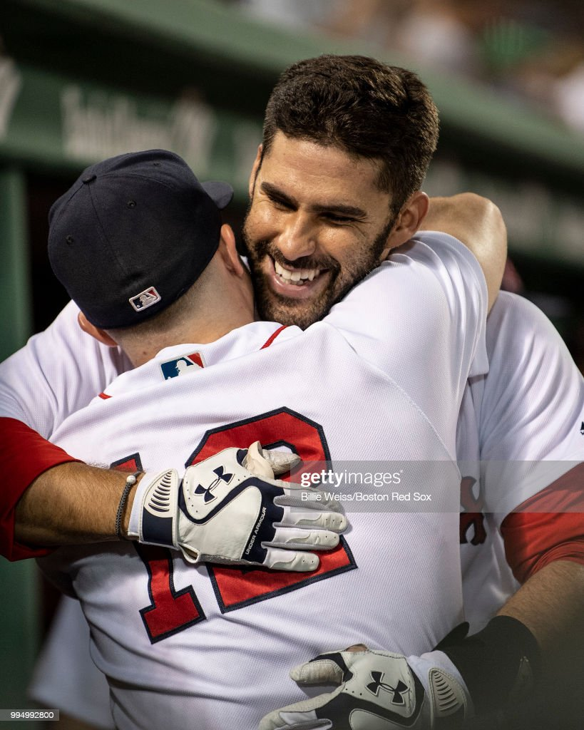 J.D. Martinez #28 of the Boston Red Sox hugs Brock Holt #12 after hitting a three-run home run during the eighth inning of a game against the Texas Rangers on July 9, 2018 at Fenway Park in Boston, Massachusetts.