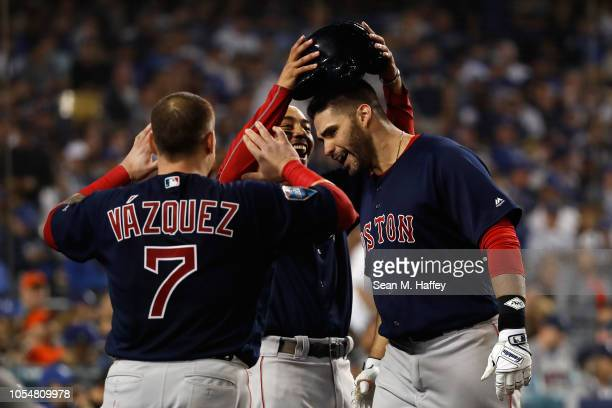 D Martinez of the Boston Red Sox is congratulated by his teammates Christian Vazquez and Mookie Betts after his seventh inning home run against the...