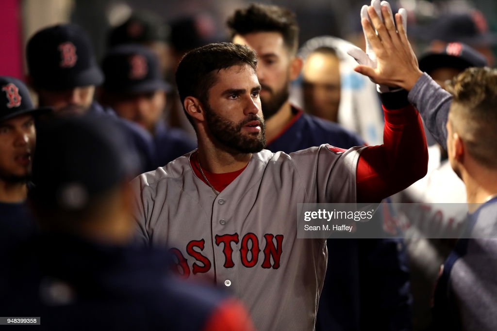 J.D. Martinez #28 of the Boston Red Sox is congratulated in the dugout after hitting a solo homerun during the seventh inning of a game against the Los Angeles Angels of Anaheim at Angel Stadium on April 18, 2018 in Anaheim, California.