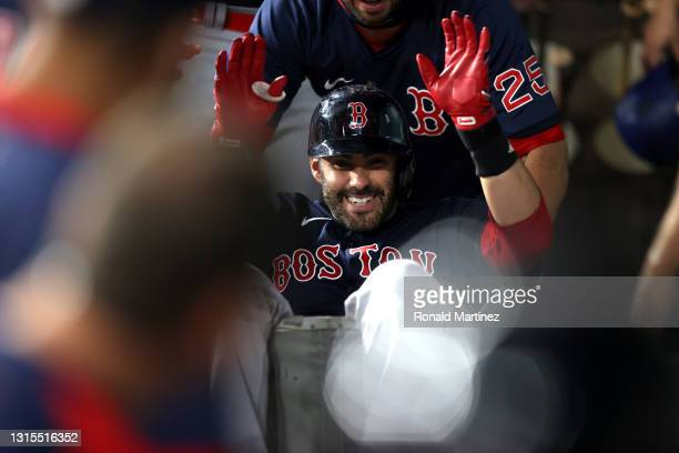 Martinez of the Boston Red Sox is pushed in a laundry cart after hitting a three-run homerun against the Texas Rangers in the first inning at Globe...