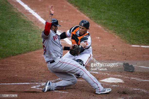 Martinez of the Boston Red Sox is tagged out at home plate by Pedro Severino of the Baltimore Orioles during the inning at Oriole Park at Camden...