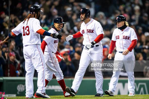 D Martinez of the Boston Red Sox reacts with Brock Holt Mookie Betts and Hanley Ramirez after hitting a grand slam home run during the fifth inning...