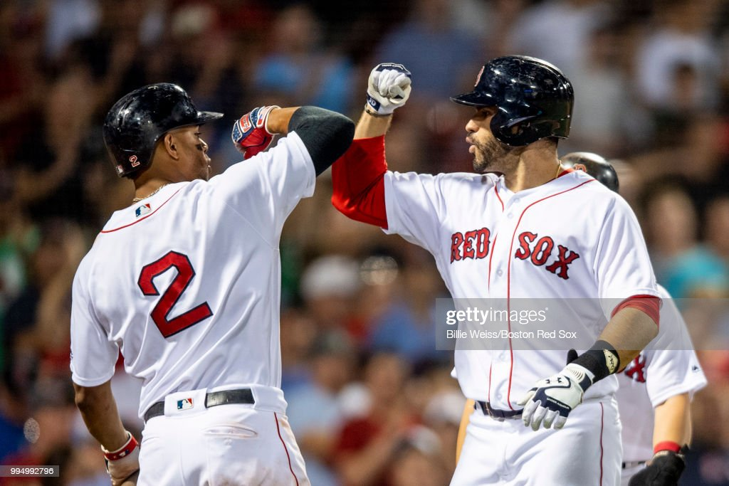 J.D. Martinez #28 of the Boston Red Sox reacts with Xander Bogaerts #2 after hitting a three-run home run during the eighth inning of a game against the Texas Rangers on July 9, 2018 at Fenway Park in Boston, Massachusetts.