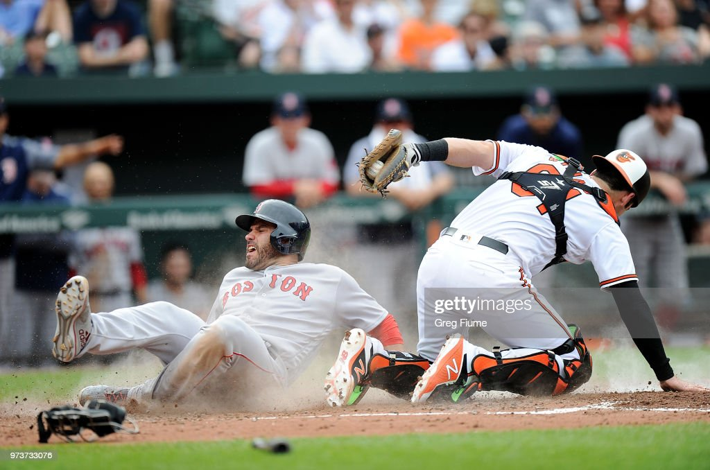 J.D. Martinez #28 of the Boston Red Sox scores in the fifth inning ahead of the tag of Austin Wynns #61 of the Baltimore Orioles at Oriole Park at Camden Yards on June 13, 2018 in Baltimore, Maryland.