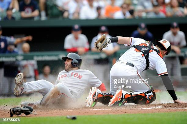 D Martinez of the Boston Red Sox scores in the fifth inning ahead of the tag of Austin Wynns of the Baltimore Orioles at Oriole Park at Camden Yards...