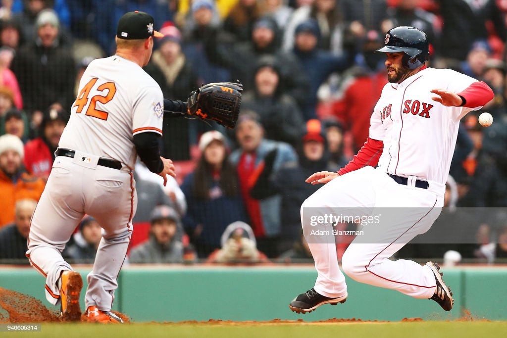 J.D. Martinez #28 of the Boston Red Sox scores on a wild pitch as Dylan Bundy #37 of the Baltimore Orioles attempts to tag him out in the sixth inning of a game at Fenway Park on April 15, 2018 in Boston, Massachusetts. All players are wearing #42 in honor of Jackie Robinson Day.