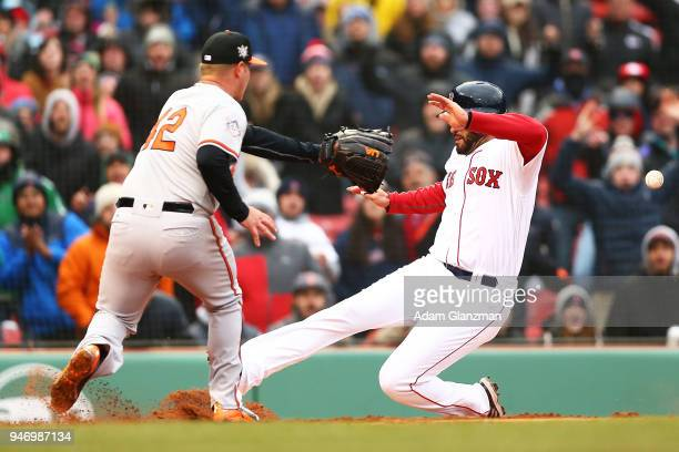 D Martinez of the Boston Red Sox scores on a wild pitch as Dylan Bundy of the Baltimore Orioles attempts to tag him out in the sixth inning of a game...
