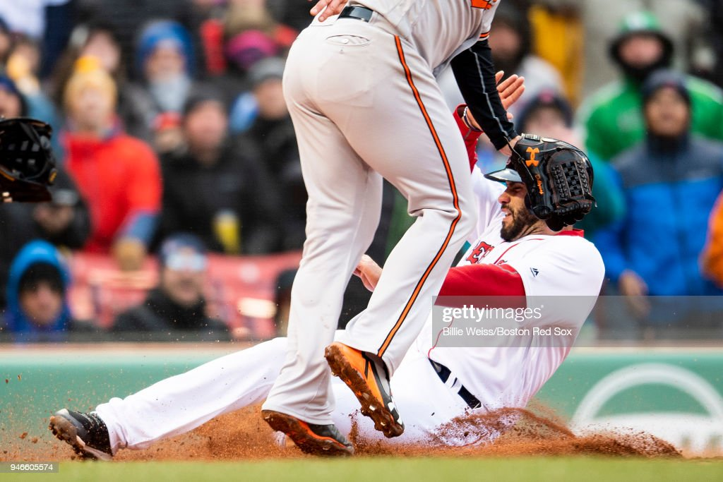 J.D. Martinez #28 of the Boston Red Sox slides as he scores on a wild pitch during the sixth inning of a game against the Baltimore Orioles on April 15, 2018 at Fenway Park in Boston, Massachusetts.