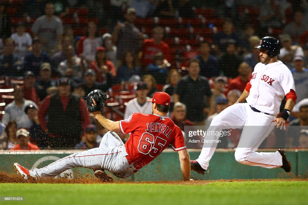 J.D. Martinez #28 of the Boston Red Sox slides safely into home plate as Jake Jewell #65 of the Los Angeles Angels injures his right ankle as he slides into home plate in an attempt to tag out Martinez in the eighth inning of a game at Fenway Park on June 27, 2018 in Boston, Massachusetts.