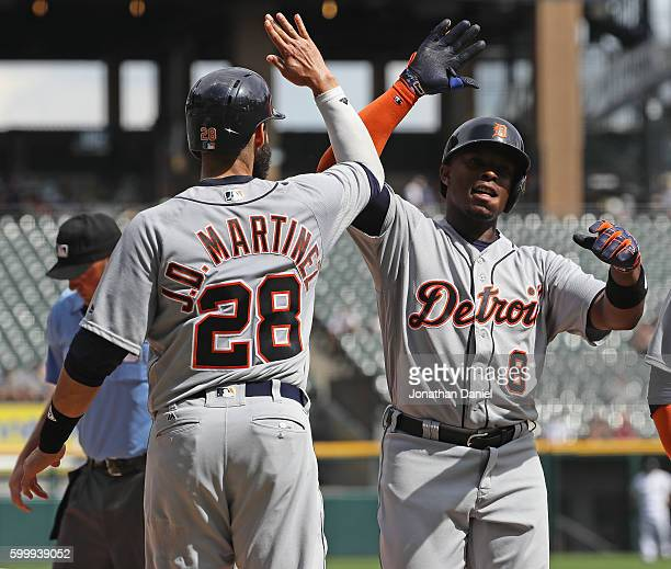 D Martinez of the Detroit Tigers congratulates Justin Upton after Upton hit a three run home run in the 2nd inning against the Chicago White Sox at...