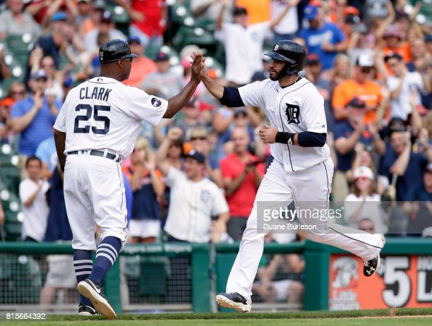 D Martinez of the Detroit Tigers is congratulated by third base coach Dave Clark of the Detroit Tigers after hitting a solo home run during the...