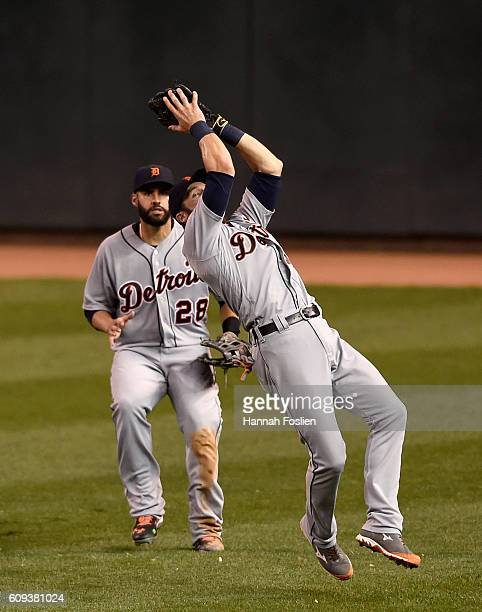 D Martinez of the Detroit Tigers looks on as teammate Andrew Romine makes a catch of the ball hit by John Ryan Murphy of the Minnesota Twins during...