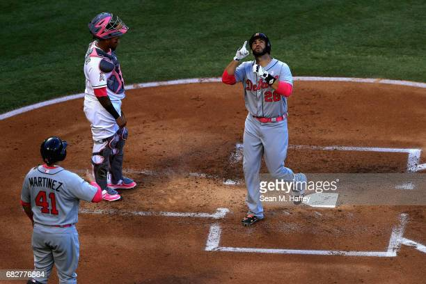 D Martinez of the Detroit Tigers points to the sky after hitting a tworun homerun as teammate Victor Martinez greets him at the plate with Martin...