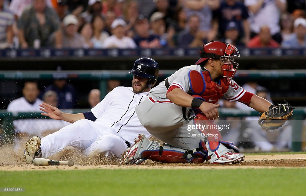 J.D. Martinez #28 of the Detroit Tigers scores from second base on a single by Victor Martinez of the Detroit Tigers, beating a tag from catcher Carlos Ruiz #51 of the Philadelphia Phillies, during the sixth inning at Comerica Park on May 24, 2016 in Detroit, Michigan.