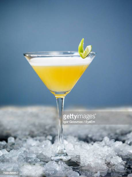 Martini Cocktail In Glass On Crushed Ice Against Blue Background