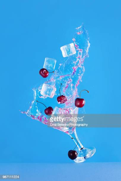 martini glass with ice cubes and cherries on a bright blue background with copy space. high-speed photography with dynamic splash. refreshing cocktail concept - freezing motion photos stock pictures, royalty-free photos & images