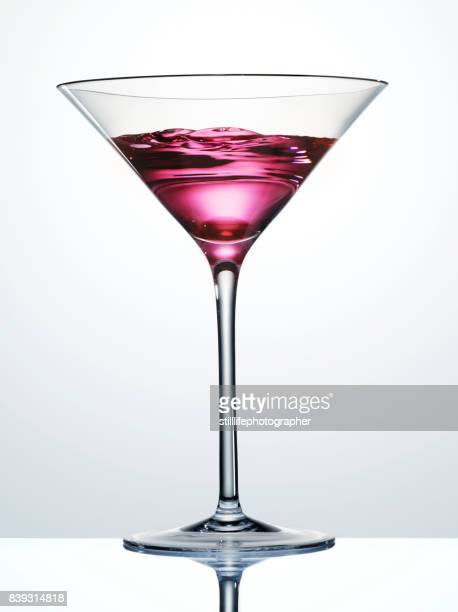 Martini Glass with swirling pink liquid inside