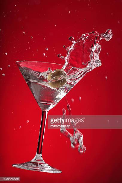 martini splashing on red background - martini glass stock photos and pictures