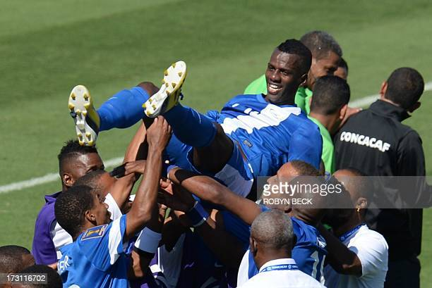 Martinique's Fabrice Reuperne is thrown in the air by his teammates after his last minute goal defeated Canada in the 2013 CONCACAF Gold Cup opener...