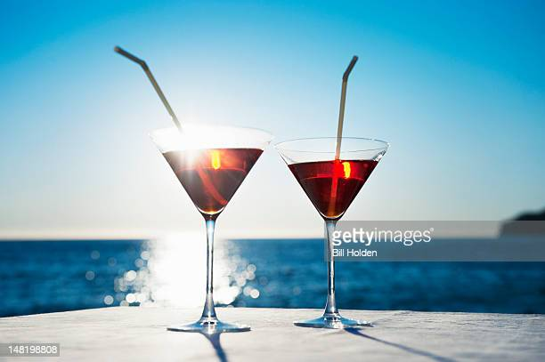 Martinis with straws on table outdoors