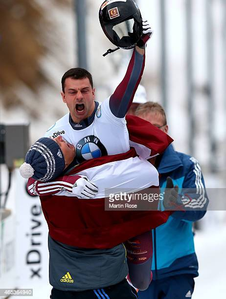 Martins Dukurs of Latvia celebrates after winning the world championship after his fourth run of the men's skeleton competition during the FIBT Bob &...