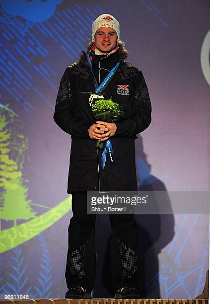 Martins Dukurs of Latvia receives the silver medal during the medal ceremony for the men's skeleton held at the Whistler Medals Plaza on day 9 of the...