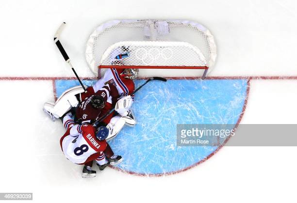 Martins Karsums of Latvia gets tangled up with Michal Barinka and Ondrej Pavelec of Czech Republic in front of the net in the second period during...