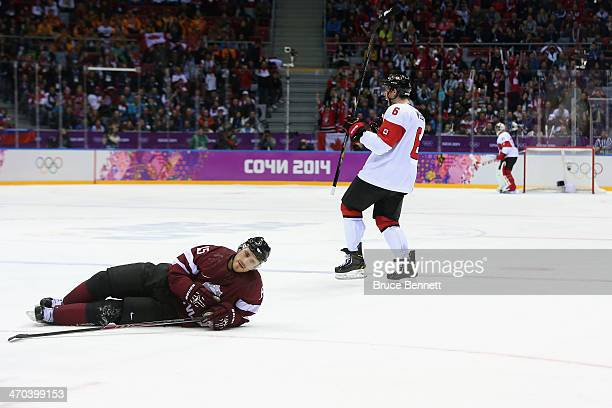 Martins Karsums of Latvia reacts as Shea Weber of Canada celebrates his thirdperiod goal during the Men's Ice Hockey Quarterfinal Playoff on Day 12...