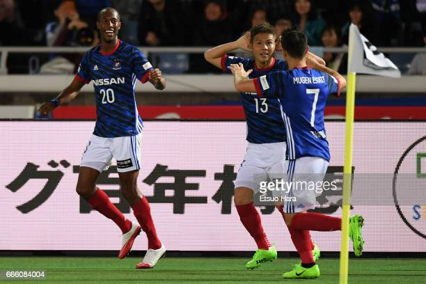 Martinus of Yokohama F.Marinos celebrates scoring the opening goal with his team mates Hugo Vieira and Takashi Kanai of Yokohama F.Marinos during the...