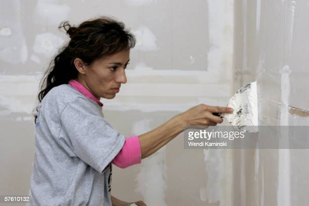 Martiza Jacobo spackles drywall in the garage of her new home during a workday to contribute her 500 hours part of the requirement to receive the...